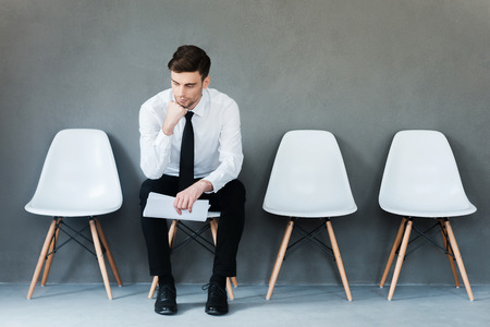 hand job: Long time of waiting. Pensive young businessman holding paper and holding hand on chin while sitting on chair against grey background