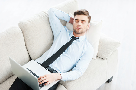 Work that makes him sleepy. Top view of young businessman sleeping and holding hand behind head while laying on sofa photo