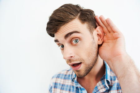 listening ear: I want to know everything! Curious young man holding hand behind ear and looking at camera while standing against white background