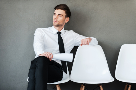 man in chair: Time of waiting. Thoughtful young man holding paperwhile sitting on chair against grey background