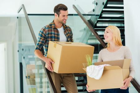cajas de carton: Feliz de hacer todo juntos. Joven pareja feliz celebración de cajas de cartón, mientras que bajando las escaleras