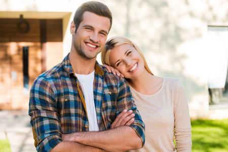parejas jovenes: Feliz pareja de j�venes. Joven pareja feliz uni�n entre s� y sonriendo mientras est� de pie en contra de su nueva casa Foto de archivo