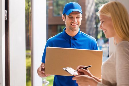 パッケージの署名。クリップボードに署名を入れて美しい若い女性ながら段ボール箱を持って笑顔の若い配達人