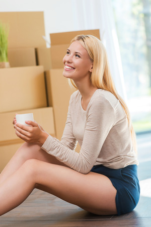 young woman sitting: Time for inspiration. Beautiful young woman sitting on the floor and holding cup of coffee while cardboard boxes laying in the background