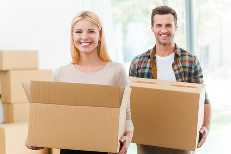 boite carton: Le passage � une nouvelle maison ensemble. Enthousiaste jeune couple tenant des bo�tes en carton tandis que d'autres bo�tes en carton pose sur fond