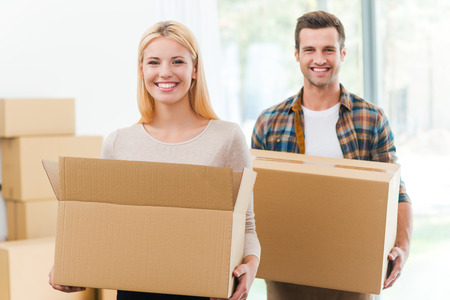 moving up: Moving to a new house together. Cheerful young couple holding cardboard boxes while other carton boxes laying on background