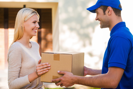 항상 시간에 도착한다. 집 앞에 서있는 동안 젊은 여자 골판지 상자를주고 행복 젊은 배달 남자의 측면보기
