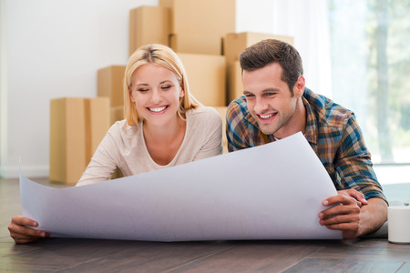 Planning their new home together. Joyful young couple laying on the floor of their new apartment and looking through blueprint while cardboard boxes laying in the background Imagens