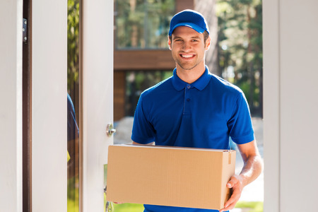 cardboard box: Delivery with smile. Cheerful young courier holding a cardboard box while standing at the entrance of apartment