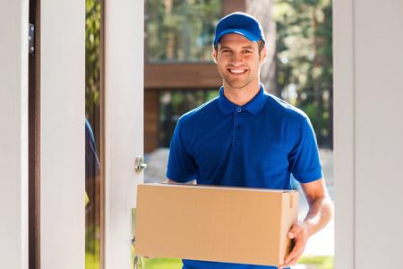 boite carton: Livraison avec le sourire. Enthousiaste jeune courrier tenant une boîte en carton tout en se tenant à l'entrée de l'appartement Banque d'images