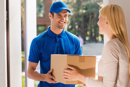 Fast and reliable service. Cheerful young delivery man giving a cardboard box to young woman while standing at the entrance of her apartment
