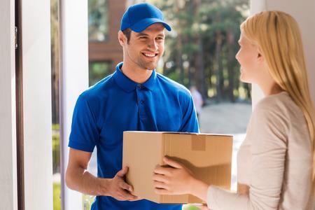 cajas de carton: Servicio r�pido y fiable. Hombre de salida joven alegre que da una caja de cart�n a la mujer joven de pie en la entrada de su apartamento Foto de archivo