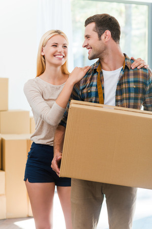real estate concept: Moving to a new house together. Happy young man holding a cardboard box while his girlfriend holding hands on his shoulders