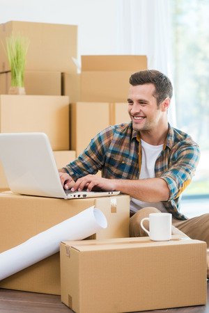 cardboard only: In search of a good design ideas. Handsome young man sitting on the floor and working on laptop while cardboard boxes laying in the background Stock Photo
