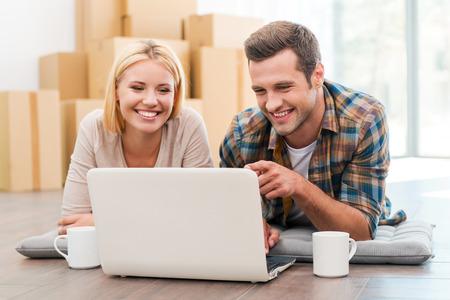 En busca de una buena empresa de mudanzas. Pareja joven alegre que pone en el suelo de su nuevo apartamento y mirando portátil mientras que las cajas de cartón que se en el fondo Foto de archivo - 41560145