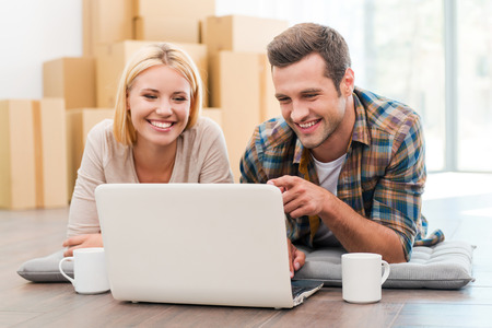 home moving: In search of a good moving company. Cheerful young couple laying on the floor of their new apartment and looking at laptop while cardboard boxes laying in the background