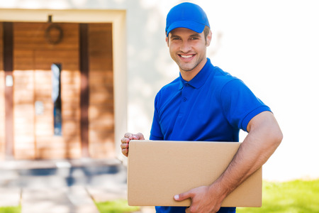 Always in time. Cheerful young delivery man holding a cardboard box while standing against residential house
