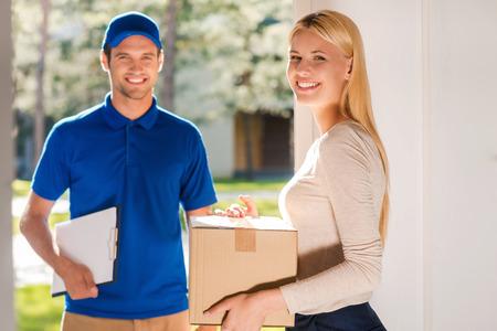 Servicio de primera clase de entrega. Mujer joven hermosa que sostiene una caja de cartón mientras que el joven portapapeles manholding entrega y sonriendo Foto de archivo