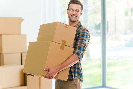 packing: Moving to a new apartment. Cheerful young man holding a cardboard boxes and smiling at camera while other carton boxes laying on background