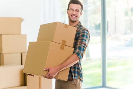 carton: Mudarse a un nuevo apartamento. Hombre joven alegre que sostiene una caja de cart�n y sonriendo a la c�mara mientras que otras cajas de cart�n que pone en el fondo Foto de archivo