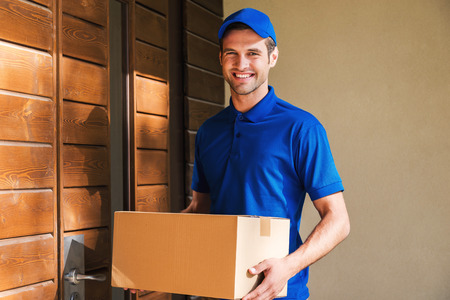 delivery box: Cheerful delivery man. Happy young courier holding a cardboard box while standing against door of residential house