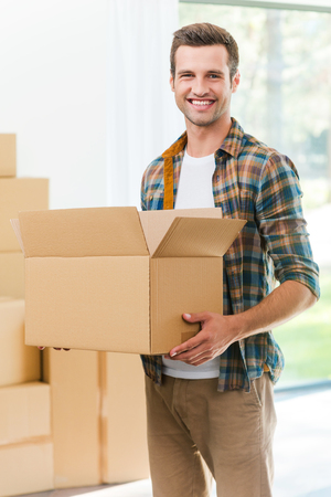 man carrying box: Happy moving to a new house. Handsome young man holding a cardboard box and smiling at camera while other carton boxes laying on background Stock Photo