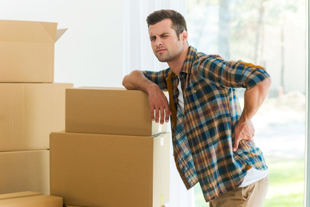 man back pain: Feeling pain in back. Frustrated young man holding hand on his back and expressing negativity while leaning at the cardboard box
