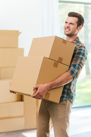 expressing negativity: Too heavy boxes. Frustrated young man carrying the heavy boxes and expressing negativity while other cardboard boxes laying in the background Stock Photo