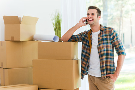 moving in: Calling from his new flat. Cheerful young man talking on the mobile phone while leaning at the cardboard box Stock Photo