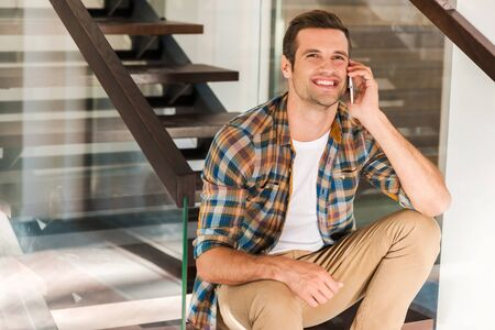 one young man: Good talk with friend. Happy young man talking on the mobile phone while sitting on staircase in his house Stock Photo