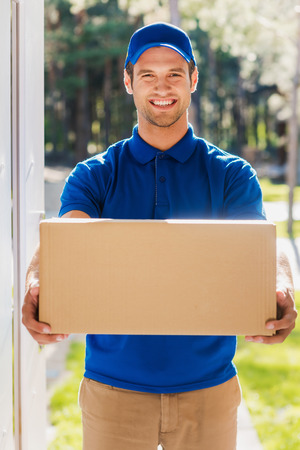 cardboard only: Take your package! Happy young delivery man stretching out a cardboard box while standing at the entrance of apartment