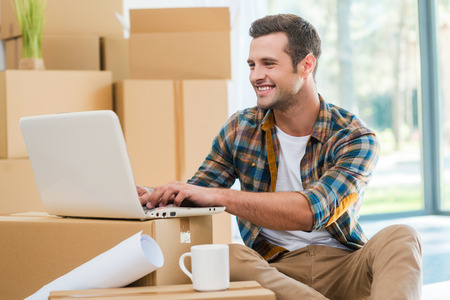 moving: Just moved in. Handsome young man sitting on the floor and working on laptop while cardboard boxes laying in the background