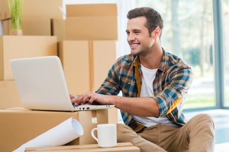 boite carton: Juste emm�nag�. Beau jeune homme assis sur le sol et le travail sur ordinateur portable tout en bo�tes de carton portant en arri�re-plan