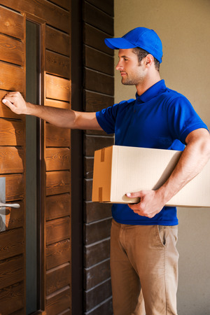 entrance door: Delivery direct to your door. Handsome young delivery man holding a cardboard box while knocking at the door of house