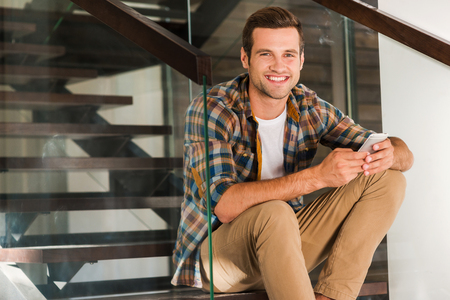 one young man: Handsome at home. Cheerful young man holding mobile phone while sitting on stairs in his house Stock Photo