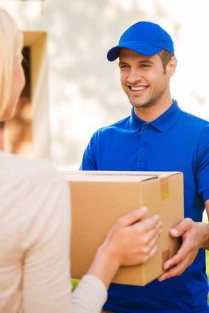 delivery box: Delivering each package with smile. Happy young courier giving a cardboard box to young woman while standing outdoors