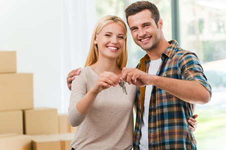 key: Keys of their new house. Cheerful young couple holding keys and smiling while standing in their new house