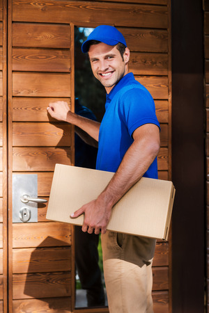 knocking: Deivery to your house. Smiling young courier holding a cardboard box while knocking at the door of residential house