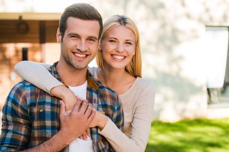 Joven y enamorado. Hermosa joven pareja uniéndose entre sí y sonriendo mientras está de pie contra su nueva casa Foto de archivo