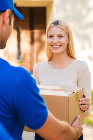 deliver: Delivery from hands to hands. Beautiful young woman smiling while young delivery man giving a cardboard box to her
