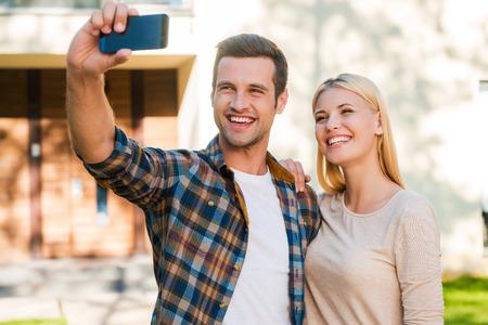 haciendo el amor: Selfie para su álbum familiar. Alegre joven pareja de unión entre sí al tiempo que selfie por teléfono inteligente mientras está de pie en contra de su nueva casa