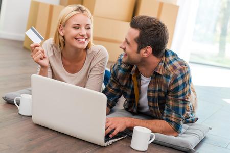 shopping: Las compras en línea hace la vida más fácil. Pareja joven y sonriente que pone en el suelo de su nuevo apartamento y compras a través de Internet, mientras que las cajas de cartón que se en el fondo