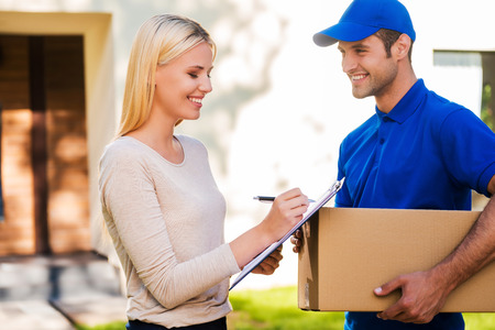portapapeles: Firme aqu� por favor! Hombre de salida sonriente joven que sostiene una caja de cart�n, mientras que la mujer hermosa joven que pone la firma en el portapapeles