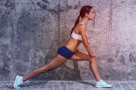 one young adult woman only: Stretching for success. Side view of beautiful young woman in sports clothing doing stretching exercises while standing in front of the concrete wall