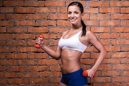 feeling good: Looking good and feeling great. Beautiful young woman in sports clothing exercising with dumbbells and smiling while standing against brick wall