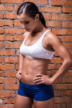 abdominal wall: She is in perfect form. Beautiful young woman in sports clothing holding hands on hip and looking down while standing against brick wall Stock Photo
