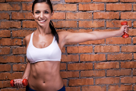 abdominal wall: Keeping her body fit. Beautiful young woman in sports clothing exercising with dumbbells and smiling while standing against brick wall