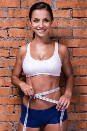 abdominal wall: Living fit and happy life. Beautiful young woman in sports clothing measuring her hip and smiling while standing against brick wall
