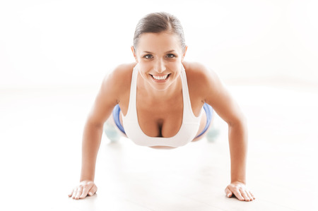sports clothing: Woman exercising. Front view of beautiful young woman in sports clothing doing push-ups Stock Photo