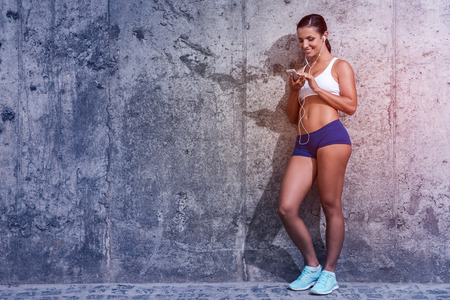 WOMAN FITNESS: Choosing music for training. Full length of beautiful young woman in sports clothing holding MP3 player and looking at it with smile while leaning at the concrete wall